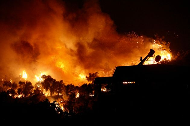 A picture taken on August 3, 2021 shows flames rising from a fire spreading in the Aegean coast city...