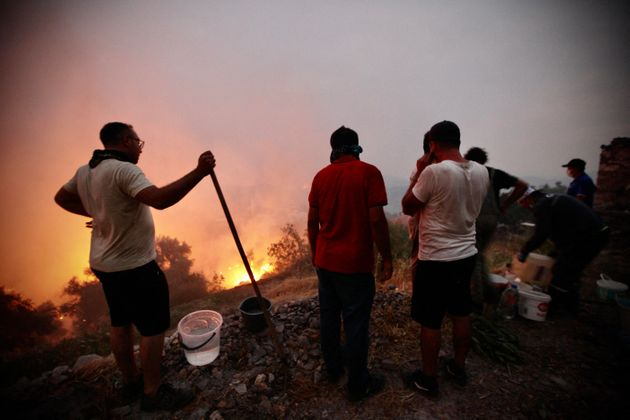 Fire crews, helped by inhabitants, work to put out a fire spreading in the Aegean coast city of Oren,...