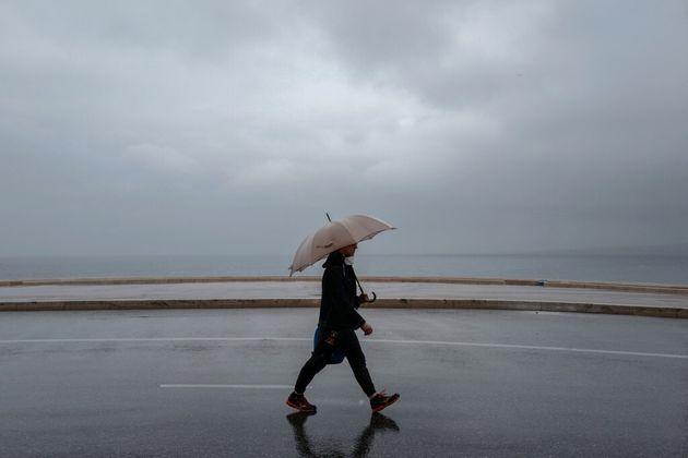 Un passant marche sous la pluie à Nice, le 19 avril