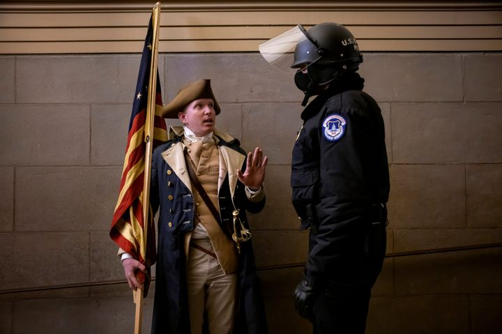 A protester dressed as George Washington debates with a Capitol Police officer on Jan. 6, 2021.