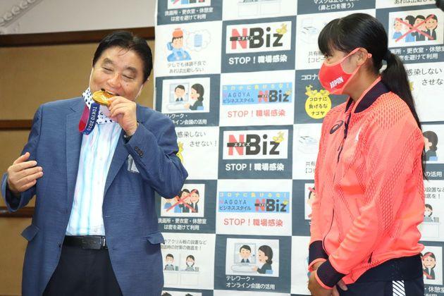 ソフトボール女子五輪代表の後藤希友投手(右)の表敬訪問を受け、首に掛けてもらった金メダルにかみつく名古屋市の河村たかし市長=4日午前、同市役所