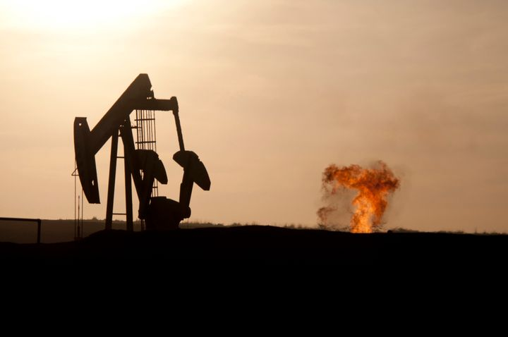 An oil well jack pump and a natural gas flare-off at sunset in the Bakken oil field north of Williston, North Dakota.