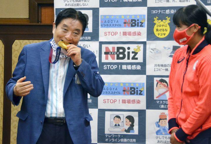 Nagoya city Mayor Takashi Kawamura bites the Olympic gold medal of softball pitcher Miu Goto during a ceremony in Nagoya on Aug. 4.