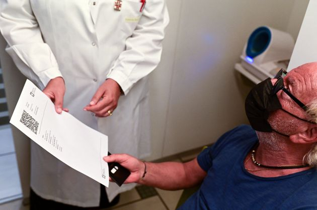 Zacco Cataldo, 70 years old receives a document proving his vaccination against the Covid-19, on August 5, 2021 at the Ambreck pharmacy, in Milan. - The Green Pass enters into force in Italy on August 6, 2021. (Photo by MIGUEL MEDINA / AFP) (Photo by MIGUEL MEDINA/AFP via Getty Images)