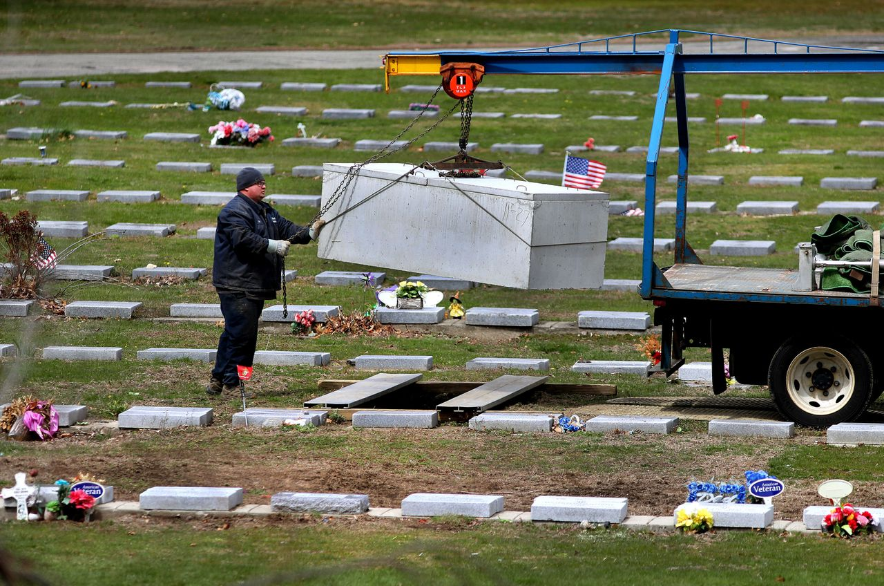 A worker lowers a concrete burial vault into a new grave at Mt. Hope Cemetery in Boston on April 22, 2020.