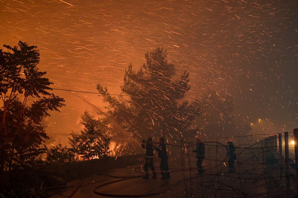 An Athens suburb is engulfed in flames during a wildfire.