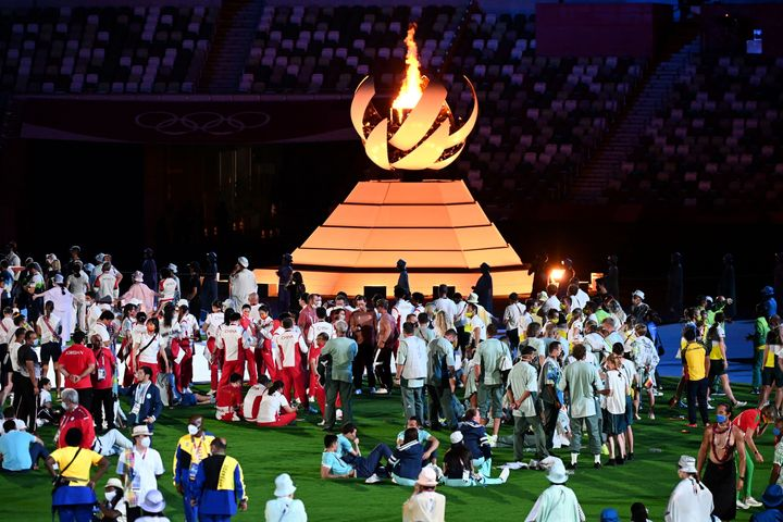 Athletes celebrate next to the Olympic Cauldron at the closing ceremony of the Tokyo Olympics.