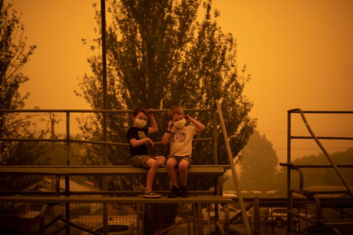Children wear masks as they play at the showgrounds in the southern New South Wales, Australia, town of Bega where people were camping after being evacuated from nearby sites affected by bushfires in December 2019.