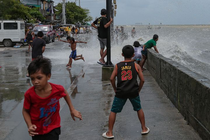 Children play in floodwater near the shore of the polluted Manila Bay in the Tondo district of Manila City in the Philippines