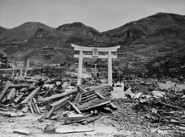 被爆にも耐え完全な形で残ったものの、喪失してしまった山王神社の一の鳥居。同鳥居の後方にある、半壊し現在も残る被爆鳥居(昭和20年秋に撮影)[長崎市国際文化会館提供]