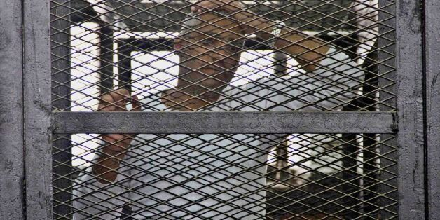 Canadian-Egyptian acting Al-Jazeera bureau chief Mohammed Fahmy appears in a defendant's cage in a courthouse near Tora priso