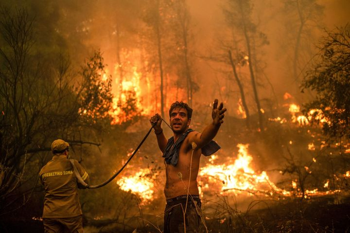 A local resident holds an empty water hose during an attempt to extinguish forest fires on Evia island in Greece.