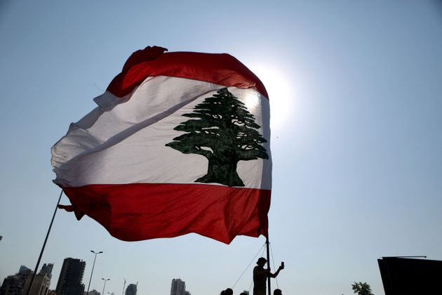 TOPSHOT - A Lebanese flag waves during a remembrance ceremony at the port of Lebanon's capital Beirut on August 4, 2021, on the first anniversary of the blast that ravaged the port and the city. - Hundreds of Lebanese marched on August 4 to mark a year since a cataclysmic explosion ravaged Beirut, protesting impunity over the country's worst peacetime disaster at a time when its economy was already in tatters. (Photo by PATRICK BAZ / AFP) (Photo by PATRICK BAZ/AFP via Getty Images)