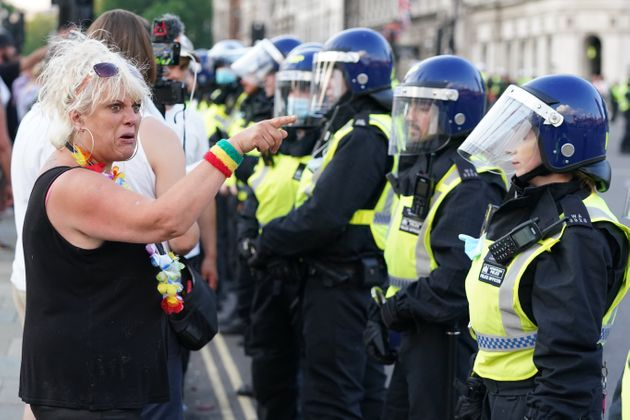 Police maintain a cordon as anti-vaccination protesters look on during a demonstration in Parliament...