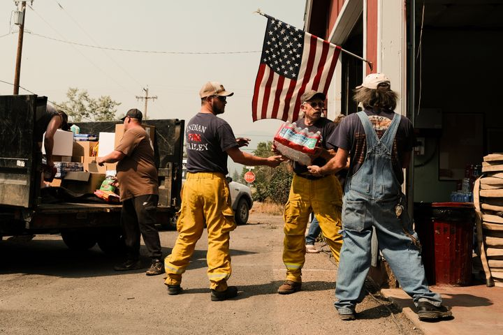 Volunteers haul in supplies to the fire station situated on Nelson Street to serve residents that defied evacuation orders on August 8, 2021 in Taylorsville, California.