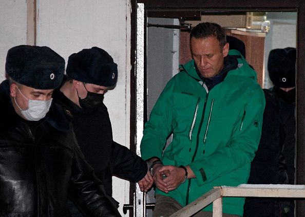 Opposition leader Alexei Navalny is escorted out of a police station on January 18, 2021