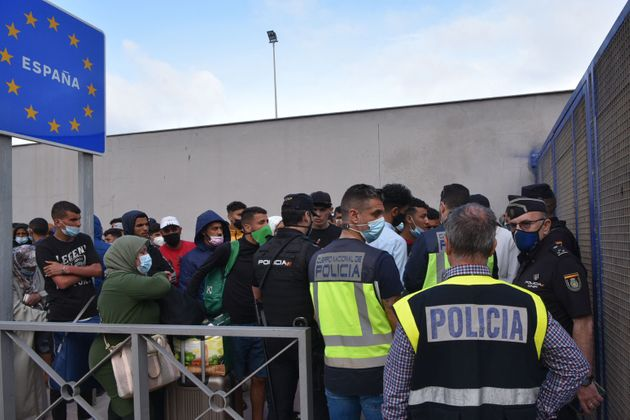 Spanish policemen stand next to migrants waiting to cross the border back to Morocco at the Spanish enclave of Ceuta on May 20, 2021