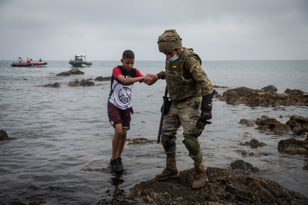 A Spanish soldier helps a migrant after he crossed the border between Morocco and Spain by swimming in May, 2021