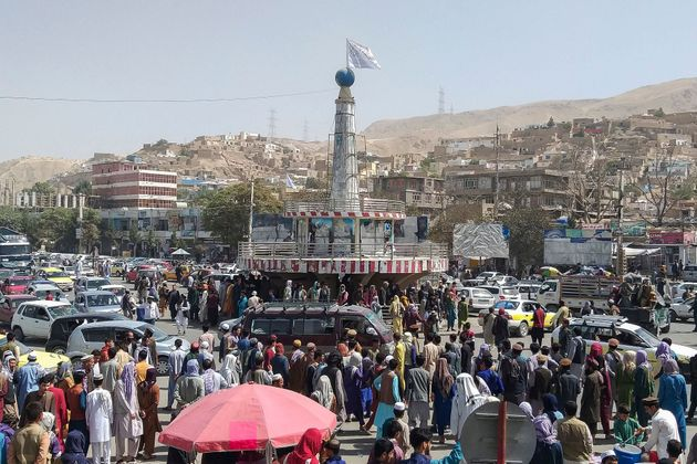 A Taliban flag is seen on a plinth with people gathered around the main city square at Pul-e-Khumri on...