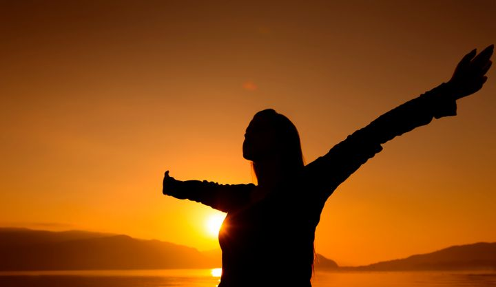 woman silhouette with arms raised, sunset shoot.