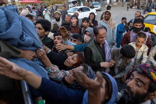 KABUL, AFGHANISTAN - AUGUST 10 : Displaced Afghans reach out for aid from a local Muslim organization...