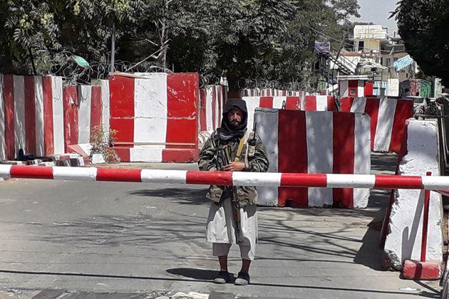 Un taliban garde l'entrée du quartier général de la police à Ghazni le 12 août 2021 après la prise de...