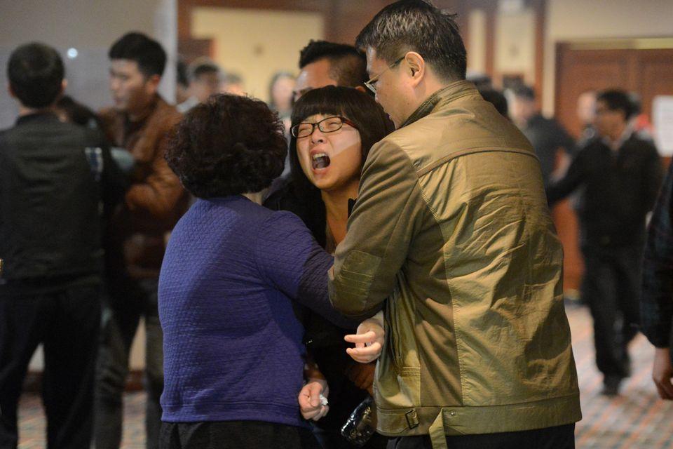 Familiares de los pasajeros del vuelo MH370 de Malaysia Airlines lloran tras escuchar las noticias de que el avión se desplom