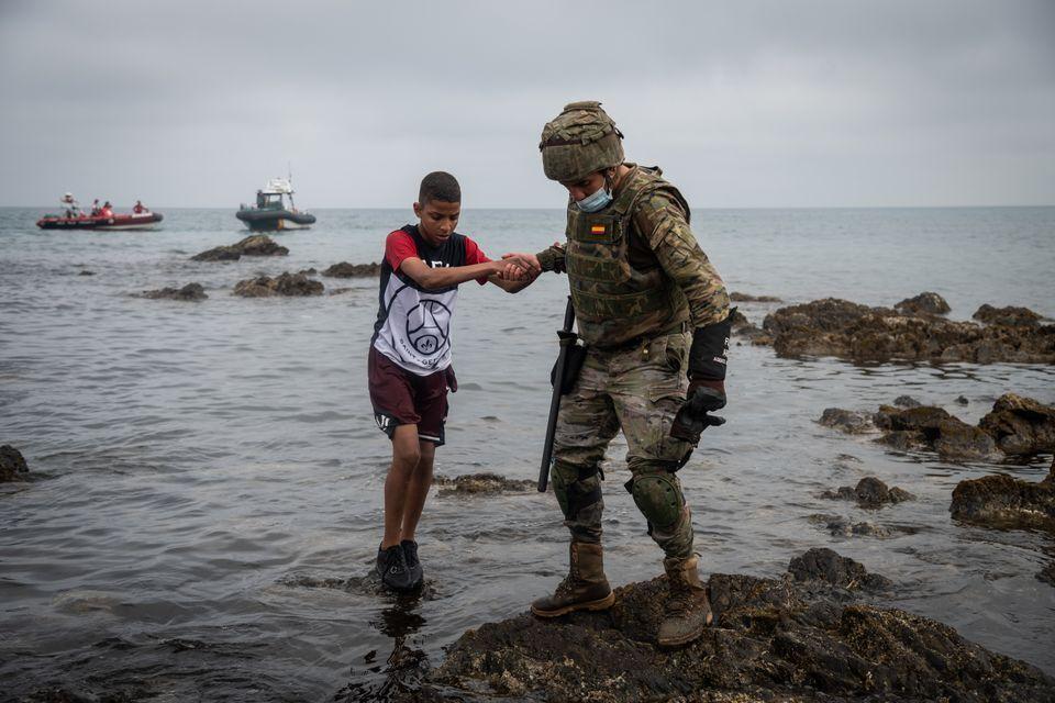 Un soldado español ayuda a un migrante adolescente recién llegado a Ceuta desde Marruecos, en mayo de