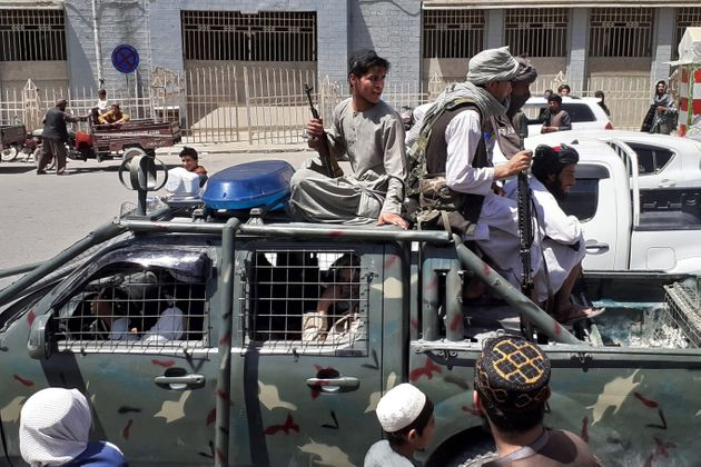 Taliban fighters are pictured in a vehicle of Afghan National Directorate of Security (NDS) on a street...