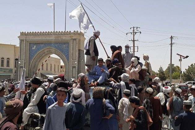 TOPSHOT - Taliban fighters stand on a vehicle along the roadside in Kandahar on August 13, 2021. (Photo...