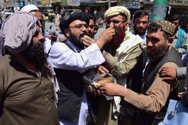 Supporters of the hardline pro-Taliban party Jamiat Ulema-i-Islam-Nazaryati (JUI-N) eat sweets as they celebrate the capture of cities in Afghanistan by the Taliban, in Quetta on August 13, 2021. (Photo by Banaras KHAN / AFP) (Photo by BANARAS KHAN/AFP via Getty Images)