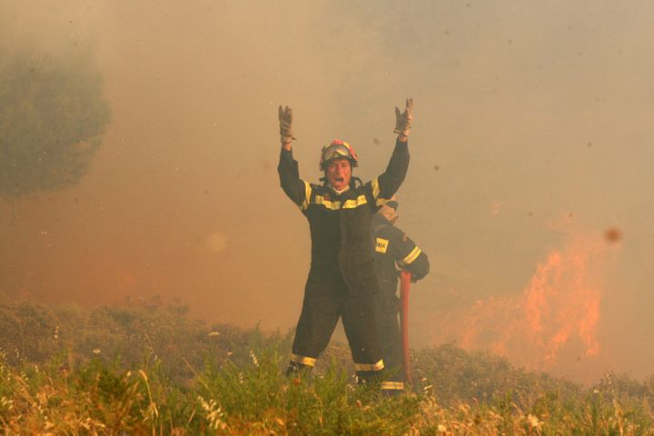 A firefighter yells while battling a forest fire in Greece.