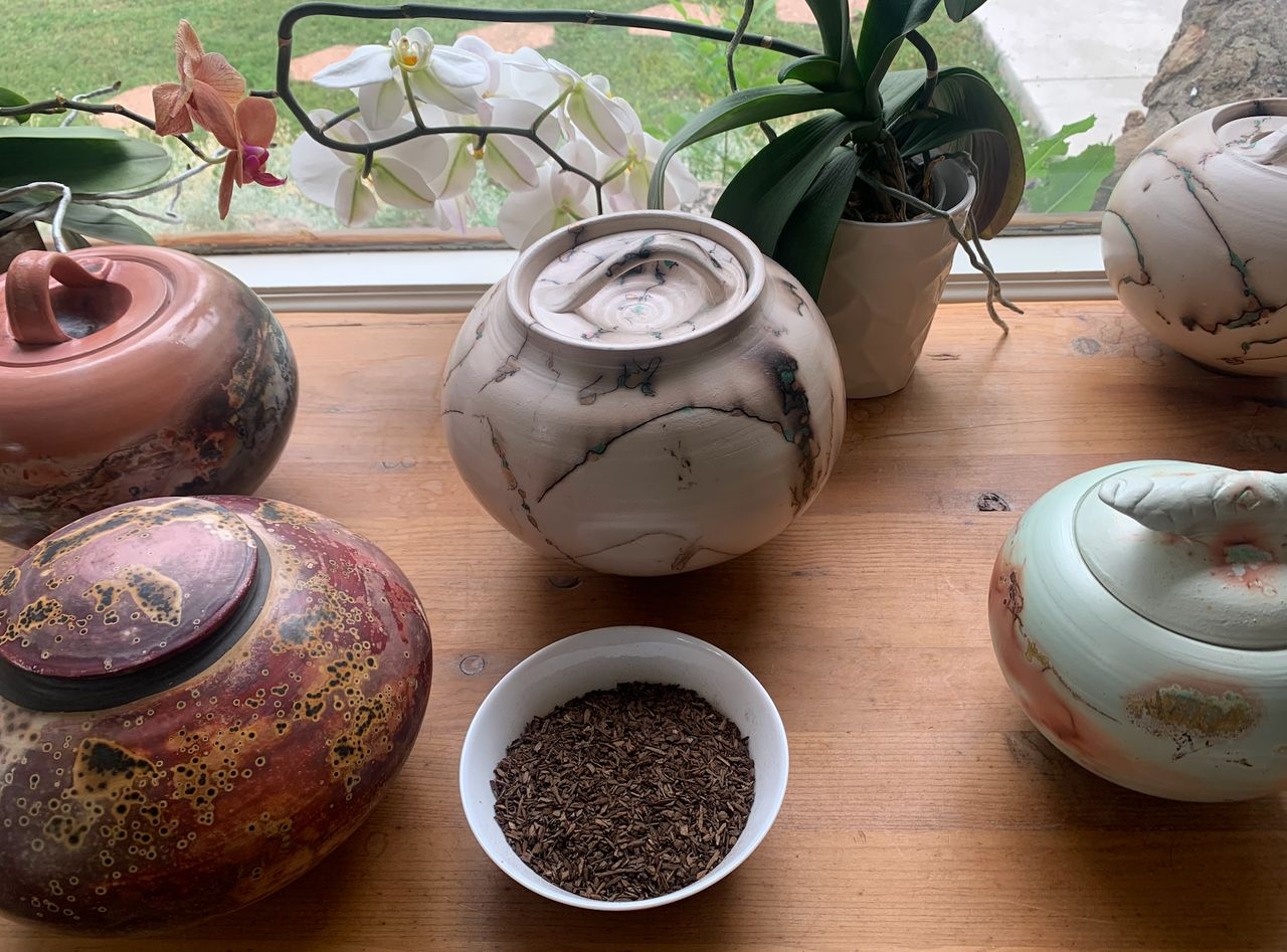 The white bowl in the foreground contains the composted remains of a pig, whose body was broken down using natural organic reduction. Human composted remains would have similar properties.
