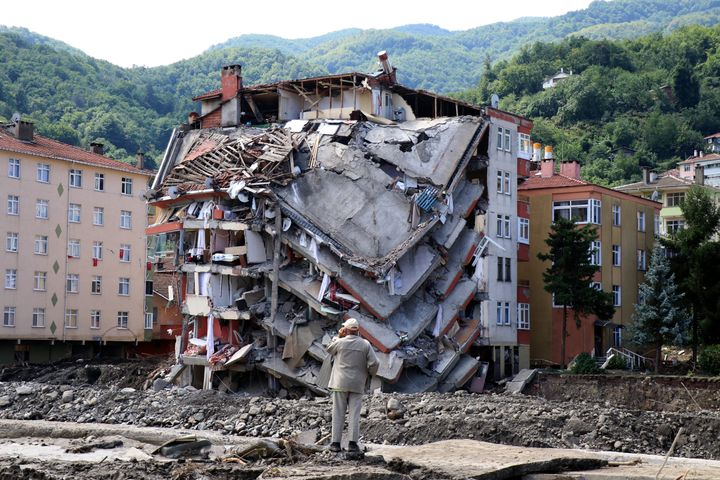 A man looks at destroyed building, in Bozkurt town of Kastamonu province, Turkey, Saturday, Aug. 14, 2021.