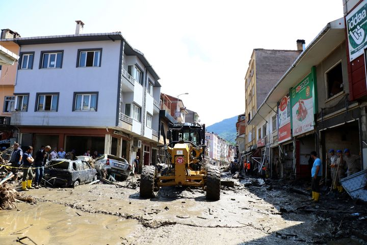 Workers clear the mud from a street in Bozkurt town of Kastamonu province, Turkey, Saturday, Aug. 14, 2021.