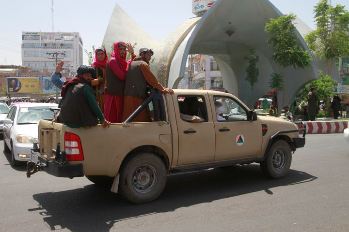 Taliban fighters pose on the back of a vehicle in the city of Herat, west of Kabul, Afghanistan, Saturday, Aug. 14, 2021, after they took this province from Afghan government.