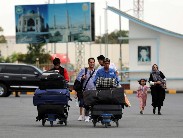 Passengers walk to the departures terminal of Hamid Karzai International Airport in Kabul, Afghanistan, Saturday, Aug. 14, 2021. (AP Photo/Rahmat Gul)