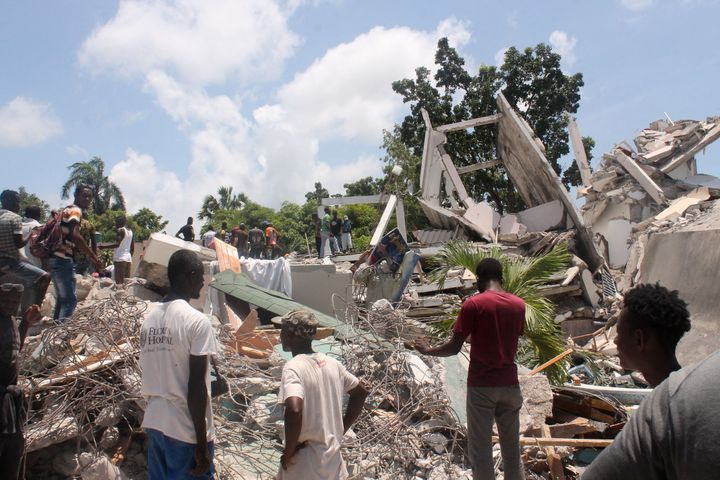 People search through the rubble of what used to be the Manguier Hotel after Saturday's earthquake.