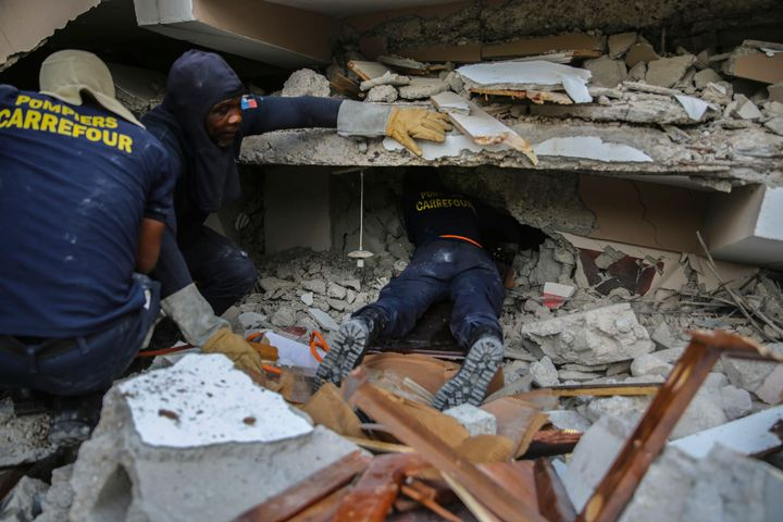 Firefighters search for survivors inside a collapsed building on Sunday.