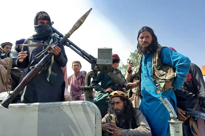 Taliban fighters sit over a vehicle on a street in Laghman province on Sunday.