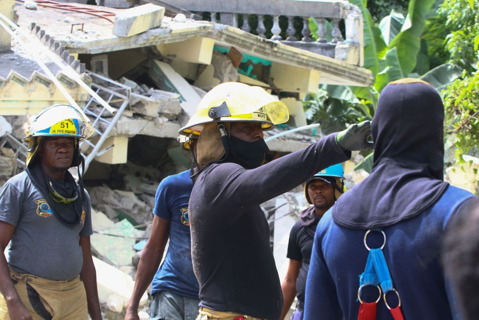 Rescue workers search through destroyed buildings in Les Cayes.