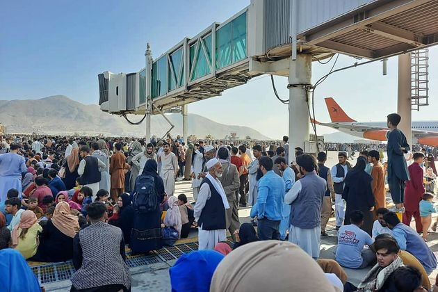 Afghans crowd at the tarmac of the Kabul airport to flee the
