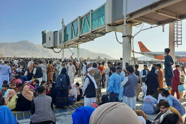 Afghans crowd at the tarmac of the Kabul airport to flee the country.