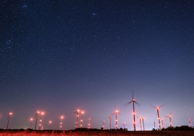 11 August 2021, Brandenburg, Petersdorf: Countless stars shine in the night sky of a brightly lit wind farm. The shooting stars of the Perseids can be seen in the night sky in the first half of August, sometimes every minute. The climax of the meteor stream is expected according to the star friends in the nights to 12. and 13. August. Who looks then with clear sky after midnight in the direction of the east, could see dozens of shooting stars per hour. Photo: Patrick Pleul/dpa-Zentralbild/ZB (Photo by Patrick Pleul/picture alliance via Getty Images)