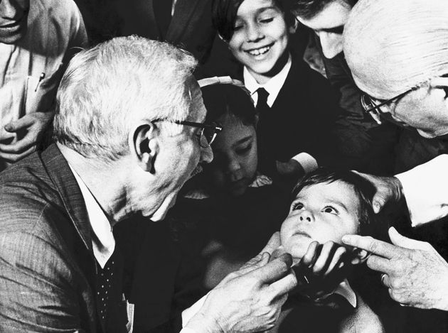 (Original Caption) Dr. Albert Sabin, who discovered a polio vaccine, asks five-year-old Luiz Inacio Gama to open wide please at the anti-polio Jesus hospital. Dr. Sabin and his wife, Jane, visited the institution and stopped in at a ward where children suffering from polio are treated.