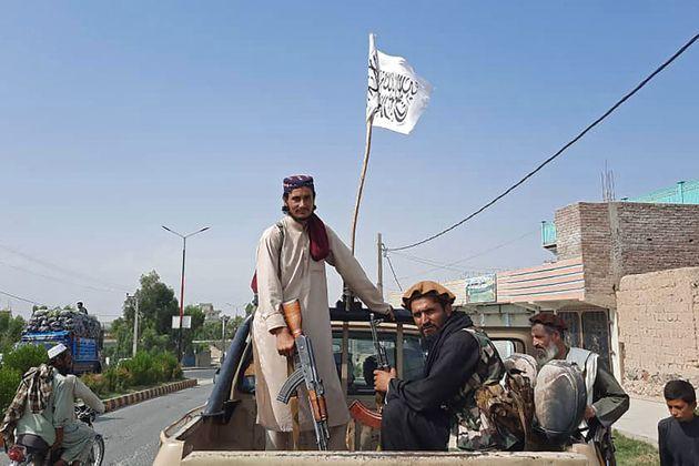 Des combattants talibans conduisent un véhicule de l'armée nationale afghane dans les rues de la province...
