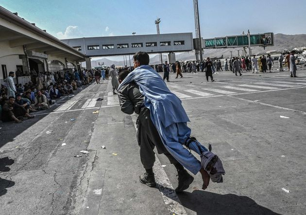 A volunteer carries an injured man as other people can be seen waiting at the Kabul airport on August...