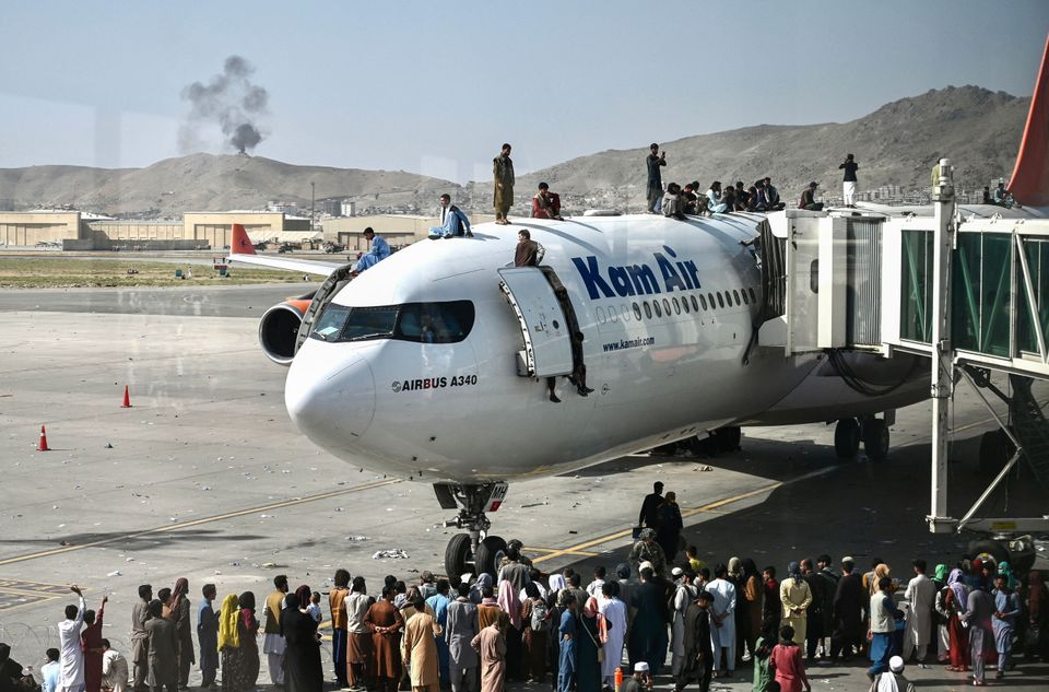 Afghan people climb atop a plane as they wait at the Kabul airport in Kabul on August 16,