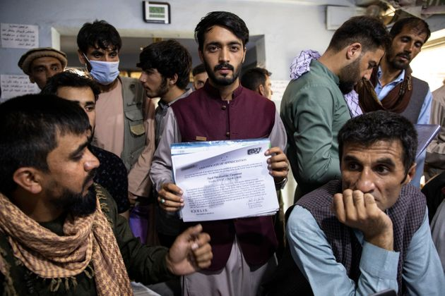 A man shows a certificate of appreciation from an American defense contractor while seeking help with...