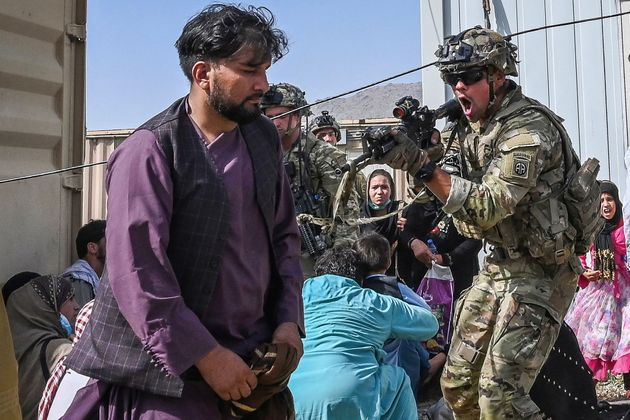 A US soldier point his gun towards an Afghan passenger at the Kabul